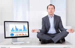 Businessman Mediating By Computer On Desk